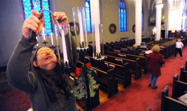 Cindy Lufkin, sexton at St. John's Episcopal Church, lights the pew torches before Christmas Eve services Tuesday in Bangor.