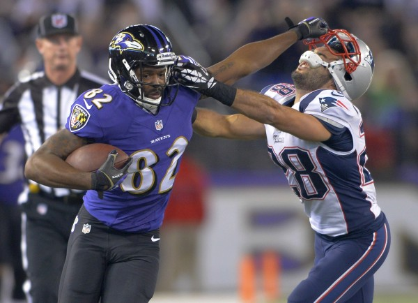 Baltimore Ravens wide receiver Torrey Smith provides a stiff arm to New England Patriots strong safety Steve Gregory after making a reception during the second half of their game in Baltimore on Sunday.