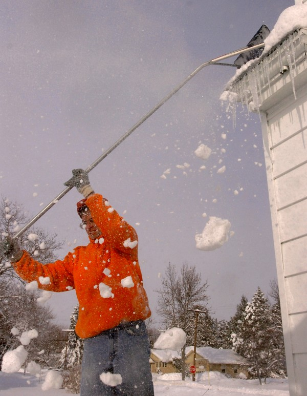 John Koskie of Bangor turns away from the falling snow as he rakes the roof of his Bangor home in 2008.