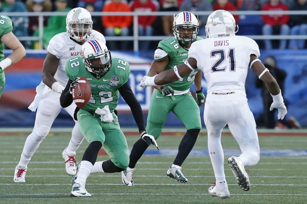 Marshall quarterback Rakeem Cato (12) runs with the ball in front of Maryland Terrapins defensive back Sean Davis (21) in the second half of Friday's Military Bowl at Navy Marine Corps Memorial Stadium in Annapolis, Md. The Thundering Herd won 31-20.
