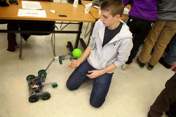A remote controlled robot gives Evan Peaco of Portland High School   a ball Tuesday in Brunswick at a robotics competition. The University of Maine Brunswick engineering program, in partnership with Southern Maine Community College, hosted the robotics and engineering event.