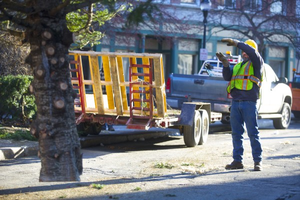 Andrew Carter directs a bucket lift operator while placing the 2013 holiday tree in West Market Square Wednesday morning. The tree was donated to the city by Sprague's Nursery and according to Dan Sprague is 36 feet tall and about 27 years old.