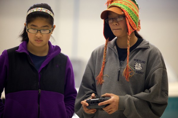 Portland High School's Robyn Ritchie (left), 16, watches as Anna Freund, 16, operates a robot at a competition in Brunswick on Tuesday. The University of Maine Brunswick engineering program, in partnership with Southern Maine Community College, hosted the robotics and engineering event.