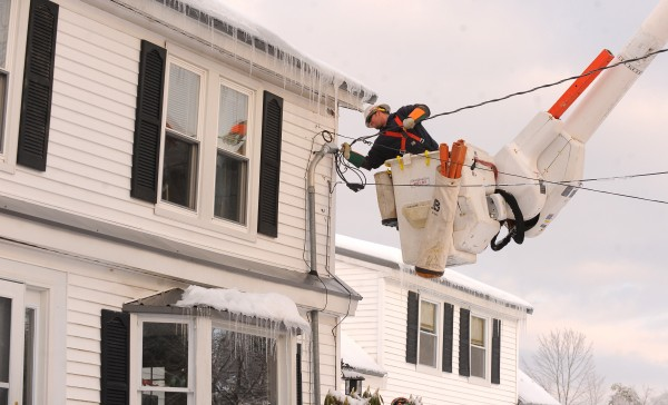 Central Maine Power line worker Matt Beeler reconnects the service cable to a home in Bucksport on Friday afternoon.  Crews continue to work on restoring power after the ice storm.