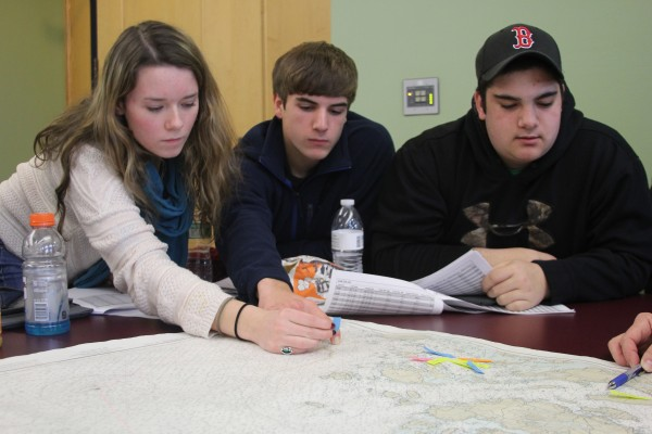 Students from George Stevens Academy marked locations where winter flounder had been caught on a nautical chart. They are among the 45 students who spent a day at Maine Maritime Academy as part of the Eastern Maine Skippers Program.