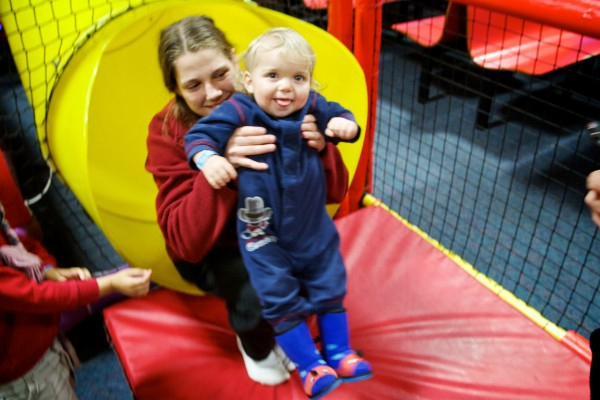 Patty Wakefield and her 16-month-old son Matthew pop out of a slide at Joker's in Portland on Wednesday. The arcade and indoor play facility opened its doors to nearly 130 parents and children from area family shelters for their third annual Christmas party.