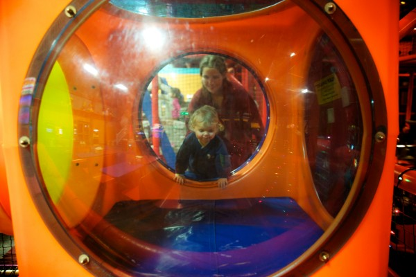 Patty Wakefield and her 16-month-old son Matthew climb through a tube at Joker's in Portland on Wednesday. The arcade and indoor play facility opened its doors to nearly 130 parents and children from area family shelters for their third annual Christmas party.