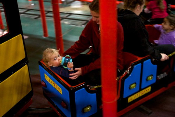 Patty Wakefield and her son Matthew, who are currently homeless, ride a train at Joker's in Portland on Wednesday. The facility opened its doors to nearly 130 parents and children from area family shelters for their third annual Christmas party.
