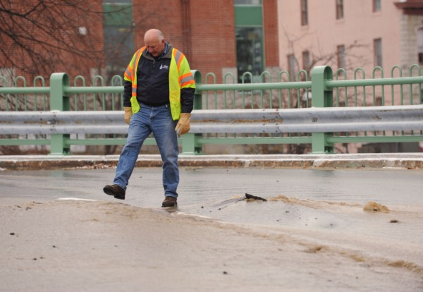 Bangor Water District service manager David Knowles inspects a section of Short Street in Bangor that has water bubbling from under it after a water main burst on Monday afternoon.