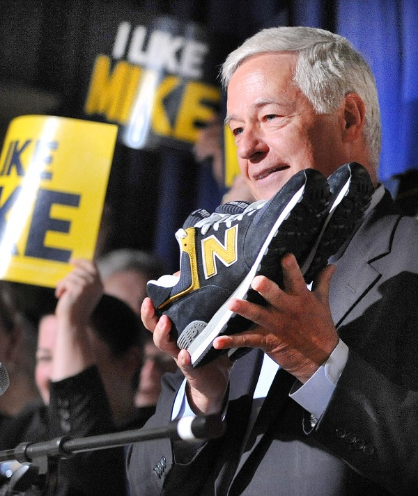 Rep. Mike Michaud holds up a pair of New Balance sneakers that he was proud to say were made here in Maine and that he would be wearing during his campaigning during his official announcement of his intention to run for governor of Maine at the Franco-American Heritage Center in Lewiston Thursday at noon.