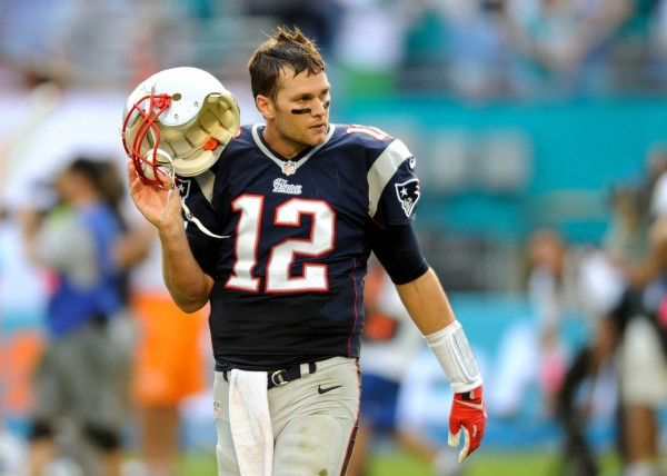 New England Patriots quarterback Tom Brady (12) takes off his helmet during the fourth quarter against the Miami Dolphins at Sun Life Stadium. The Dolphins won 24-20.