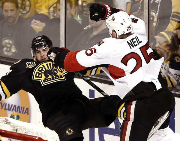 Ottawa Senators right wing Chris Neil (25) checks Boston Bruins defenseman Matt Bartkowski (43) during the second period of Friday night's game at TD Garden in Boston. The Bruins won 5-0.