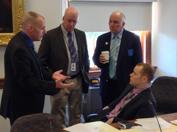 Lt. Scott Ireland (left) of the Maine State Police talks to Reps. Timothy Marks (from left), D-Pittston, Thomas Tyler, R-Windham, and Corey Wilson, R-Augusta, during a break in a subcommittee hearing on Maine concealed handgun permits at the State House in Augusta on Wednesday, Dec. 11.