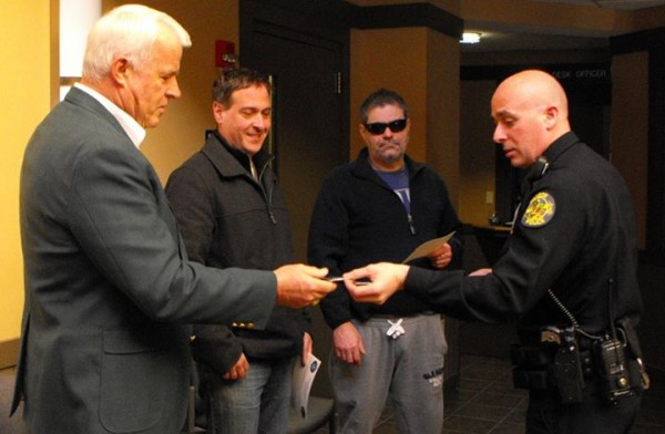 Officer Dan Sanborn (right) hands Roger Tracey of Eddington (from left), Andrew Croce of Bangor and James LaBreck of Bangor department Challenge Coins to recognize them for saving an apparently suicidal woman who was hanging off the side of the Joshua Chamberlain Bridge on Dec. 5.