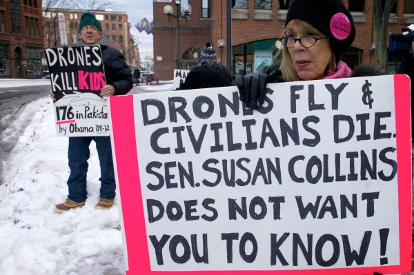Mark Roman and Pat Taub, protesters with Code Pink, demonstrate outside U.S. Sen. Susan Collins' office in Portland on Monday.
