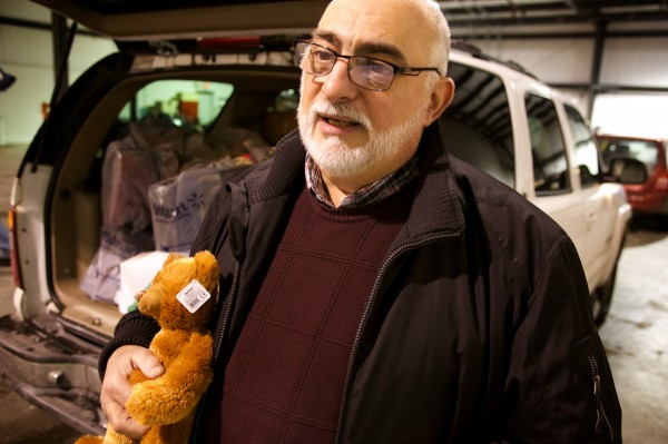 Paul Deschambeault of the Biddeford-Saco Rotary Club holds a teddy bear while other rotarians load vehicles with Christmas gifts ultimately bound for the children of Lac-Megantic, Quebec, Wednesday. Lac-Megantic suffered a catastrophic fire after an oil-laden train wrecked in July.
