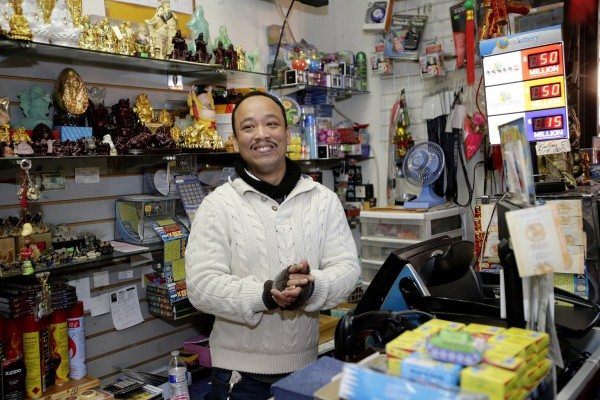 Store owner Thuy Nguyen works the front counter of his store, which sold a winning Mega Millions lottery ticket in San Jose, Calif., on Wednesday.