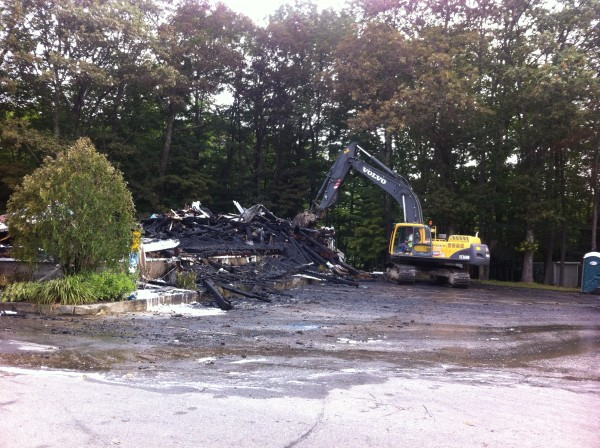An excavator demolishes the remaining charred walls of the Wescustogo Grange Hall in North Yarmouth.