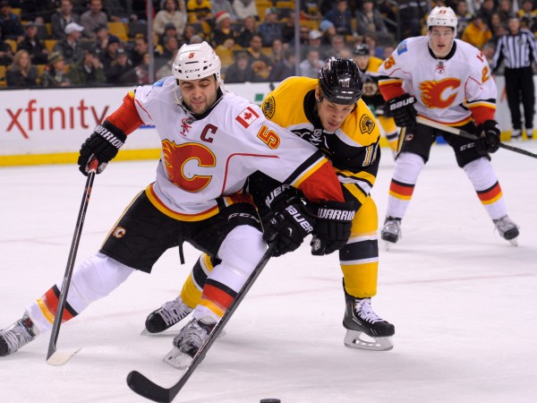 Calgary Flames defenseman Mark Giordano (5) and Boston Bruins center Gregory Campbell (11) battle for the puck during the first period at TD Banknorth Garden.