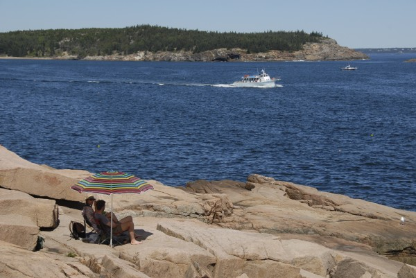 As a Bar Harbor cruise boat steams across Newport Cove, two tourists relax beneath a beach umbrella set up on the granite shoreline near Ocean Drive in Acadia National Park in this September 2012 photo.