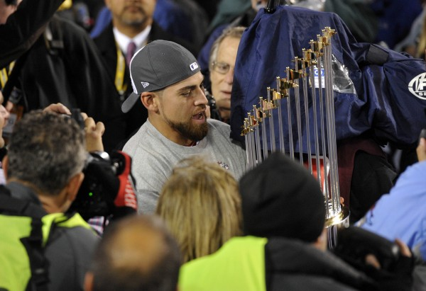 Boston Red Sox center fielder Jacoby Ellsbury carries the World Series championship trophy after game six of the World Series against the St. Louis Cardinals at Fenway Park in Boston on Oct. 30.