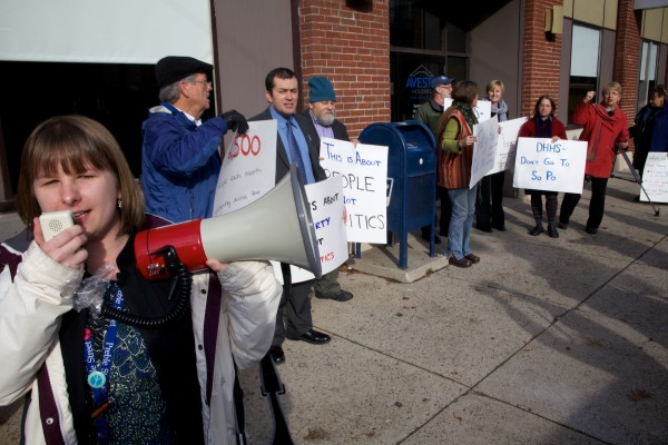 Ashley Gofczyca of Homelss Voices for Justice leads a chant in Portland Tuesday protesting the State's plan to move DHHS offices from downtown to the jetport area in South Portland.