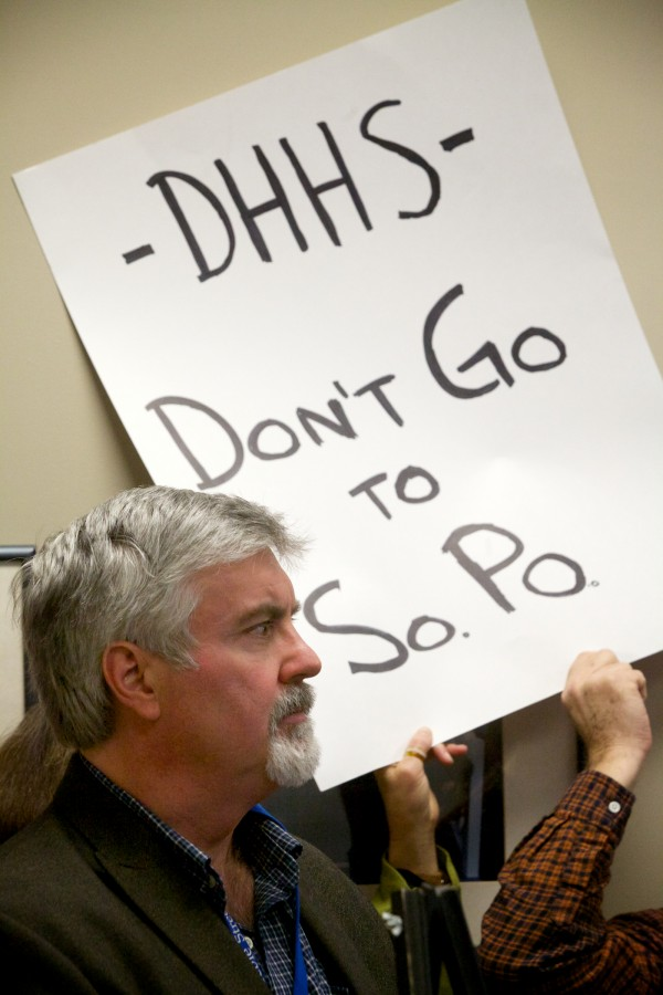 Homeless and poverty advocate Mark Swann of Preble Street listens at a press conference Tuesday in Portland as protesters speak against the state's plan to move DHHS offices out of downtown.