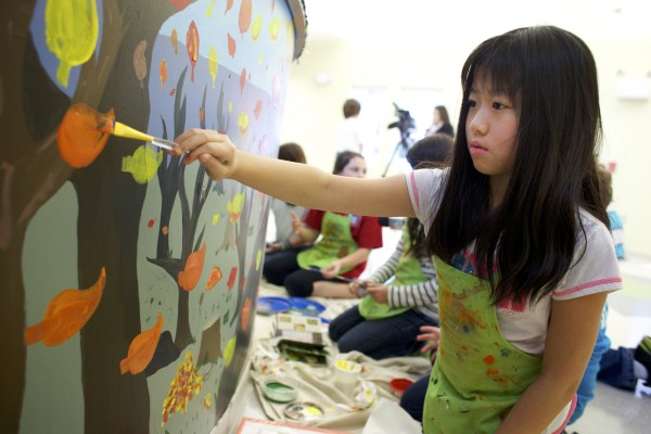 Jessica Wang, 9, paints leaves in a mural on a kitchen partition wall at the Jean Lyford Child Care Center at the new Brewer Community Center Wednesday morning in Brewer.