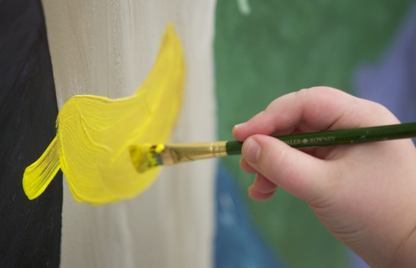 A 9-year-old paints a yellow leaf in a mural on a kitchen partition wall at the Jean Lyford Child Care Center at the new Brewer Community Center Wednesday morning in Brewer.