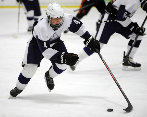 Hampden's Marc Thibodeau brings the puck down the ice against Brewer on Monday at Bangor.