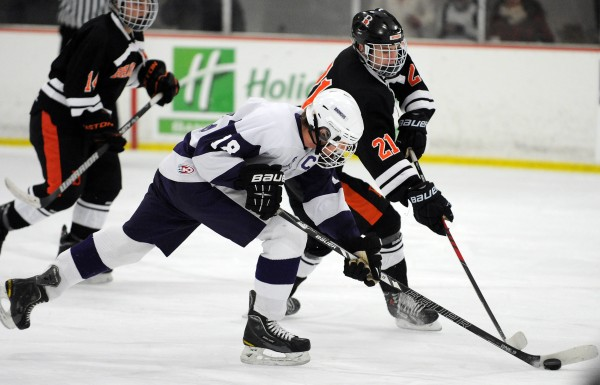 Brewer's Gehrig White and Hampden's Matt Closson battle for control of the puck on Monday at Bangor.