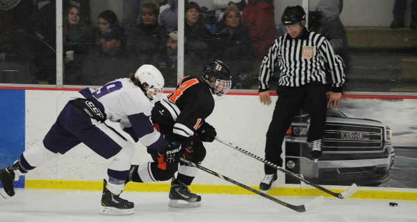 Brewer's Kyle Spox (right) and  Hampden's Michael Ward battle for control of the puck Monday at Bangor.