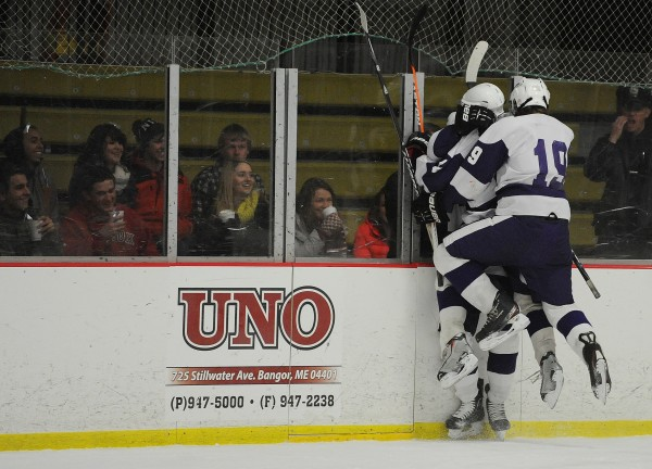 Hampden's Robert Stowe and Michael Ward jam Matt Colson against the glass after he scored an unassisted shorthanded goal against Brewer on Monday at Bangor.