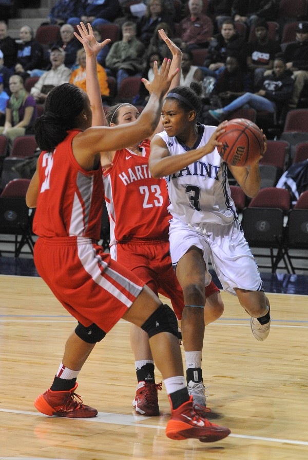 The University of Maine's Chantel Charles (right) looks up to make a pass between Hartford's Cherelle Moore (left) and Alyssa Englert during the game at the Cross Insurance Center in Bangor Wednesday.