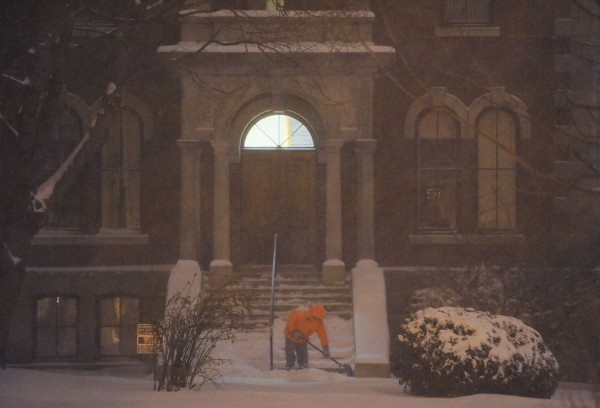 An inmate at the Penobscot County Jail shovels the steps of the sherrif's office in Bangor during pre-dawn darkness on Sunday.