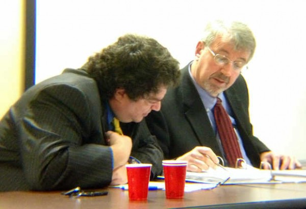 Stavros Mendros (left) reviews documents with his attorney Mark Walker during a hearing before the state's ethics commission on Thursday.