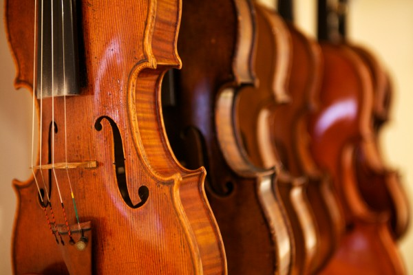 A new violin, made to look like an older one, hangs in a row with other fiddles in Jonathan Cooper's workshop in Portland on Thursday.