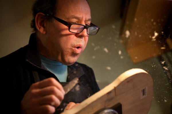 Jonathan Cooper blows shavings from the back of a violin while carving it in his Portland workshop on Thursday.