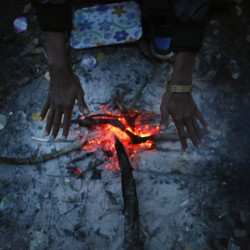An asylum seeker warms his hand over a fire in a forest near the asylum center in the village of Bogovadja, some 43 miles from Serbia's capital Belgrade November 13, 2013.
