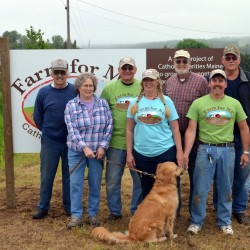 Farm for ME supporters gathered last spring to erect a sign identifying the program site. Joining in the celebration were (from left) Frank Beaulieu, neighbor and Farm for ME steering committee member; Martie Pritchard, landowner; Jim Krysiak, Catholic Charities warehouse manager; Dixie Shaw, Catholic Charities program director; Jim Pritchard, landowner; Jeff Tiner, Catholic Charities chief operations officer;  Chip Beckwith, Casella Organics field rep and Farm for ME steering committee member; and Bright, the golden retriever.