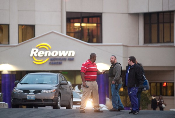 A Reno Police officer (2nd L) talks with employees of the Renown Regional Medical Center following a lockdown in Reno, Nevada December 17, 2013. A man opened fire on Tuesday in a Reno, Nevada, medical building, killing one person and injuring two others before he died of an apparently self-inflicted gunshot wound, police said.