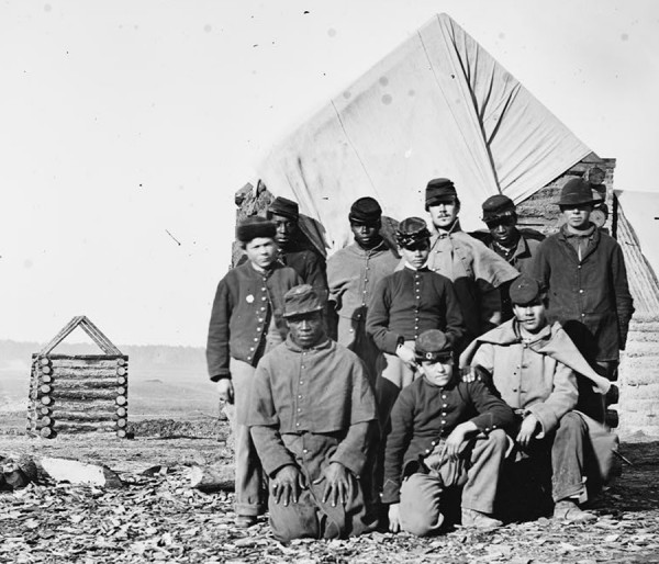 An unusual photograph taken in Virginia during the latter years of the Civil War depicts black and white Union soldiers standing together outside a rude cabin constructed in a regimental camp. The United States Army segregated units by race during the war, but historical records indicate that at least some &quotwhite&quot Maine regiments included black Maine soldiers. At least two such soldiers died while in service with such &quotwhite&quot regiments.