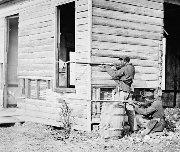 Two black Union soldiers point their rifles toward enemy lines while manning a picket post at Dutch Gap Canal in Virginia, likely sometime in spring or summer 1864.