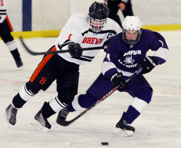 Brewer High School and Hampden Academy varsity hockey players pursue the loose puck during the Dec. 7 opening game of the 2013-14 season. Brewer won the game, 6-1, at the Penobscot Ice Arena.