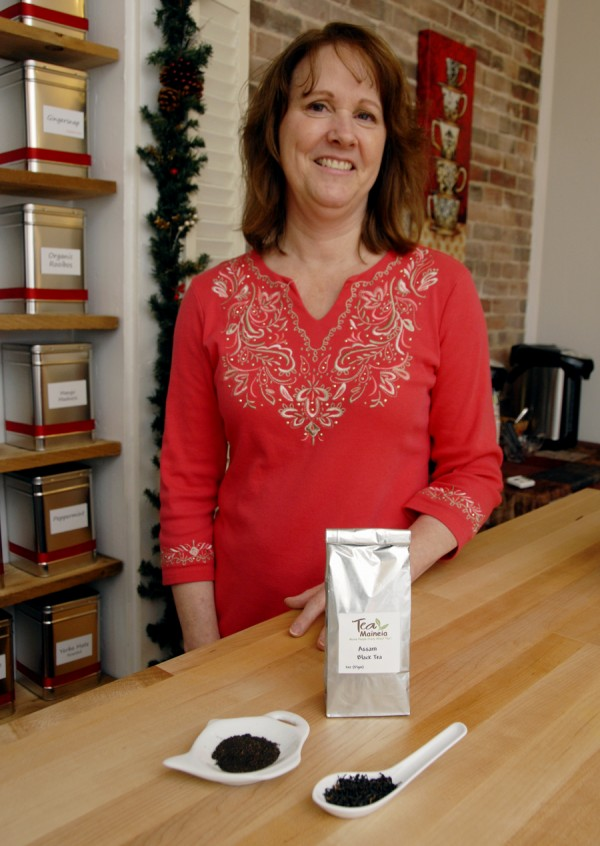 Debbie Holmes, who along with husband Dan owns Tea Maineia at 115 Main St., Winterport, displays a sample of the shop's loose-leaf Assam black tea in a spoon (right). The bowl next to the loose-leaf tea contains a sample of the tiny tea granules found in a typical tea bag.