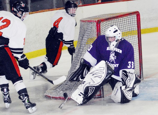 Hampden Academy goalie Ryan Manning blocks a shot by a Brewer High School skater during a Dec. 7 varsity hockey game played at the Penobscot Ice Arena in Brewer. The Witches defeated the Broncos, 6-1.