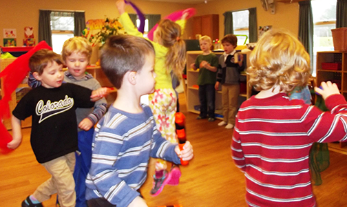 Children at Pen Bay Creative Learning Center dance and move with scarves and musical instruments inside on a rainy day.