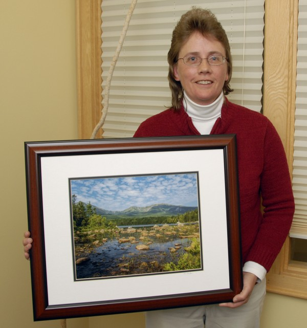 Michele Barker, a landscape and wildlife photographer who lives in Hudson, displays her landscape taken at Sandy Stream Pond on Baxter State Park. Rising above the horizon is the Great Basin of Mount Katahdin.