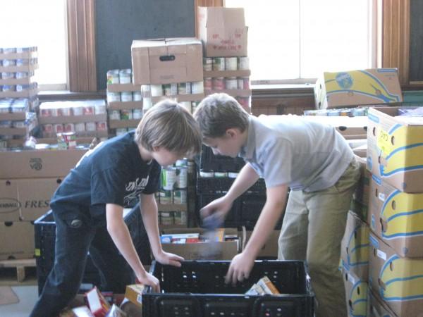 Fifth-graders Michael Stowe and Noah Morgan sort food donations.