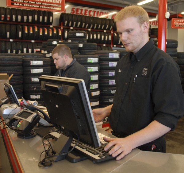 Sales associates Will Nutting (left) and Elijah Curtis work at the front counter inside the new Town Fair Auto service facility at 976 Stillwater Ave., Bangor.